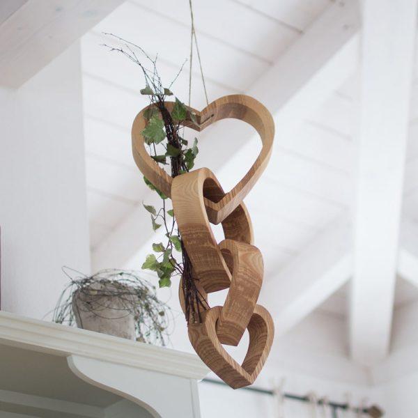 Herzen aus Holz ineinander verbunden - mit Efeu dekoriert